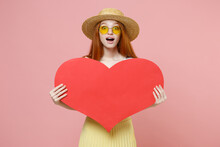 Young Surprised Redhead Ginger Romantic Happy Caucasian Woman 20s Wearing Straw Hat Glasses Summer Clothes Holding Big Red Heart Form Mock Up Isolated On Pastel Pink Color Background Studio Portrait.