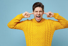 Young Caucasian Irritated Nervous Stressed Student Man With Closed Eyes In Knitted Yellow Fashionable Sweater Cover Ears With Hands Fingers Shout Scream Isolated On Blue Background Studio Portrait