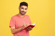 Happy positive man with beard in striped t-shirt making notes with pen at notepad, writing down information and looking at camera with smile. Indoor studio shot isolated on yellow background