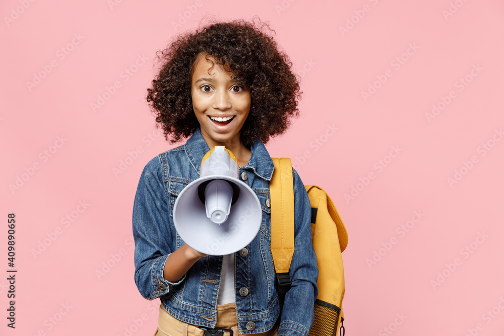 Fototapeta Smiling leader little african american kid school girl 12-13 years old in casual denim clothes with backpack scream in megaphone isolated on pastel pink background studio Childhood education concept.