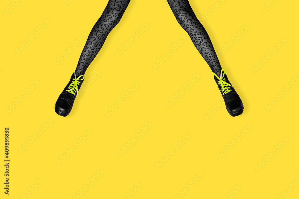 Fototapeta New gray female boots with bright yellow laces on long slender woman legs in gray tiger print tights isolated on yellow background.