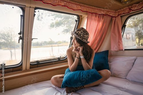 Obraz Young asian woman relaxing and looking the view in motor home on campsite at evening - fototapety do salonu