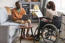 Full Length Portrait Of African-American Couple With Handicapped Woman Working From Home Together