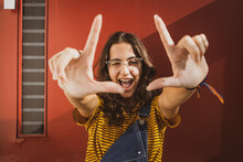 Portrait Of A Teenager Girl Wearing Clear Transparent Glasses And Colorful Clothes Making Frame Formation With Hands And Showing A Smart Comedy Face. Dark Red Door On The Background.