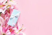 Beautiful Lilies And Gift On Color Background