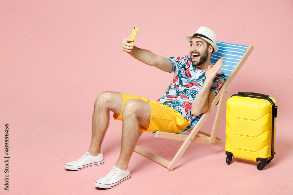 Fototapeta Full length of traveler tourist man in hat sit on deck chair doing selfie shot on mobile phone greeting with hand isolated on pink background. Passenger travel on weekend. Air flight journey concept. - obraz na płótnie