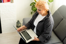 Elderly Woman Looking At Laptop. Online Video Communication With Relatives