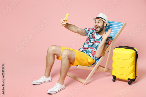 Vászonkép Full length of traveler tourist man in hat sit on deck chair doing selfie shot on mobile phone greeting with hand isolated on pink background
