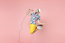 Full Length Side View Cheerful Young Traveler Tourist Man In Summer Clothes Hat Jumping Sing Song In Microphone Isolated On Pink Background. Passenger Traveling On Weekend. Air Flight Journey Concept.