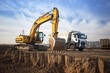 canvas print picture - huge yellow crawler excavator and a construction dump truck standing next to it while working on a sunny day against a blue sky. Emphasis on the big bucket