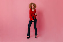 Full-length Shot Of Curly Woman In Pink Glasses Posing Against Isolated Background. Girl In Red Blouse And Stylish Jeans Dancing Disco