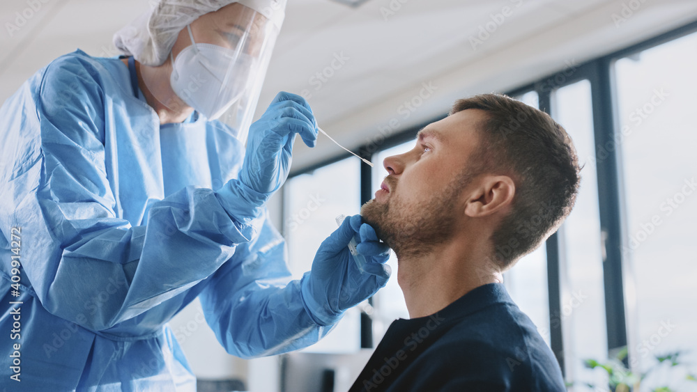 Fototapeta Medical Nurse in Safety Gloves and Mask, Protective Face Shield and Overalls is Taking a PCR Corona Virus Sample in a Health Clinic. Doctor Uses Respiratory Swab Test. Covid-19 Pandemic Concept.