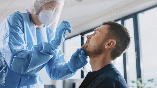 Obraz Medical Nurse in Safety Gloves and Mask, Protective Face Shield and Overalls is Taking a PCR Corona Virus Sample in a Health Clinic. Doctor Uses Respiratory Swab Test. Covid-19 Pandemic Concept. - fototapety do salonu