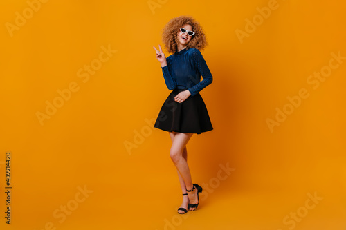 Obraz Full-length shot of charming blonde girl wearing blue top, skirt and heeled sandals. Lady in sunglasses shows peace sign on yellow background - fototapety do salonu