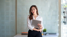Image Of An Asian Businesswoman With Confidence And Creativity. Using A Tablet At The Office.