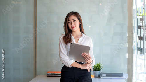 Fototapeta Image of an asian businesswoman with confidence and creativity. Using a tablet at the office. obraz
