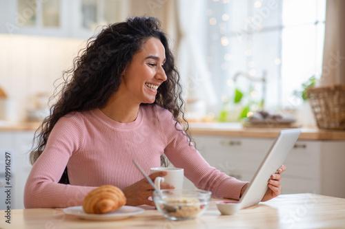 Fotografija Cheerful Brunette Lady Using Digital Tablet While Having Breakfast In Kitchen