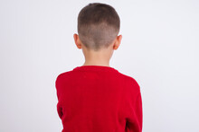 Little Cute Boy Kid Wearing Red Knitted Sweater Against White Wall Standing Backwards Looking Away With Arms On Body.