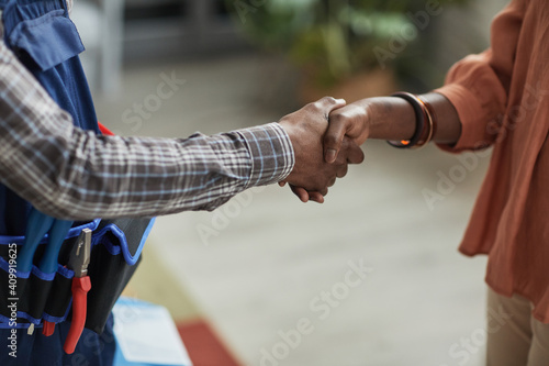 Obraz Close up of unrecognizable African-American woman shaking hands with handyman standing in home interior, copy space - fototapety do salonu