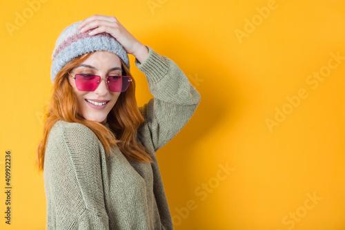 Fototapeta Happy trendy girl with sunglasses, isolated on yellow background