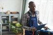 Leinwandbild Motiv Waist up portrait of African-American handyman looking at camera while standing with toolbox in home interior, copy space