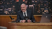 Late-night Talk Show Host Sitting Behind His Table And Performing His Monologue, Looking Into Camera. TV Broadcast Style Show