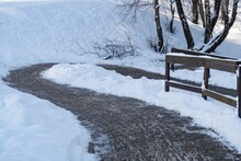 Winding And Slippery Footpath With Massive Wooden Railing In A Snowy Park, Winter Background