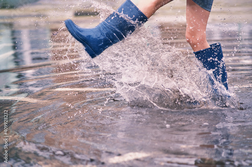 Obraz na płótnie Female legs in rubber boots in a huge puddle scatter splashes