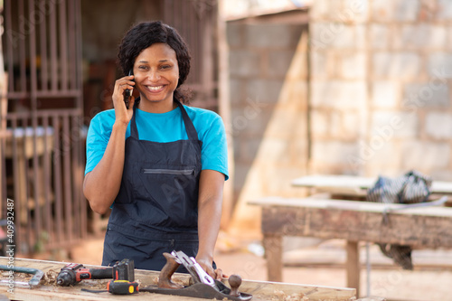 Fotografia female african carpenter smiling while making a phone call