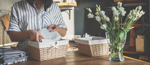 Obraz Girl spring cleaning in the kitchen. Piles kitchen towels in baskets. Spring cleaning, decluttering, cleaning space, cleaning agency - fototapety do salonu