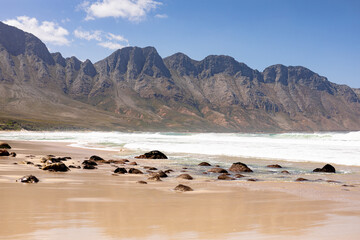 Beautiful beach by the sea and mountains with rocks and golden sand on a sunny day