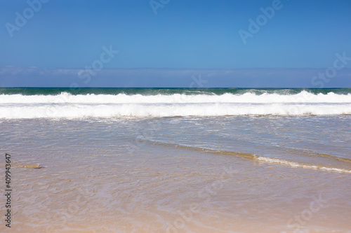 Beautiful beach by the sea and with big waves and golden sand on a sunny day