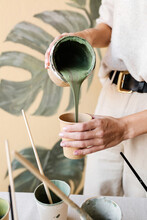 Cropped Unrecognizable Female Artist In Mask Pouring Paint In Cup And Mixing Colors For Creating Monstera Leaves On Wall At Home