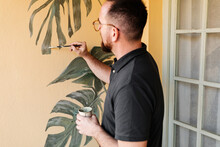 Side View Of Talented Male Artist Painting Green Monstera Leaves On Wall In Apartment