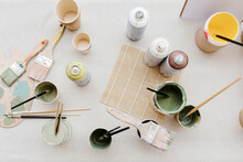 Top View Of Various Paint And Brushes Placed On Table In Creative Workshop