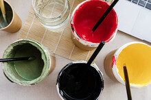 From Above Of Set Of Paints Of Various Colors And Paintbrushes Arranged On Table In Creative Art Studio