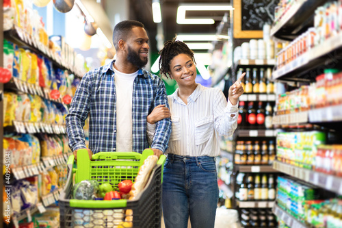 Cheerful Black Spouses Choosing Food In Grocery Store Fotobehang