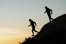 Side View Of Silhouettes Of Unrecognizable Runners Training In Rocky Terrain In Highlands At Sundown In Summer