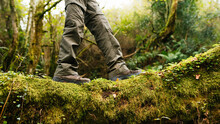 Side View Of Legs Of Crop Explorer In Trekking Boots Standing On Mossy Ground In Forest During Summer Adventure