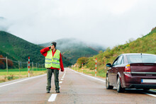 Female Driver In Reflective Vest Standing On Road Near Broken Car In Mountainous Area And Talking On Smartphone While Calling For Help