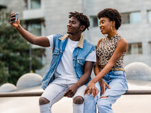 Cheerful Young African American Man And Woman With Curly Hair Dressed In Trendy Ripped Jeans Sitting On Fence And Taking Selfie On Smartphone While Spending Time Together In City