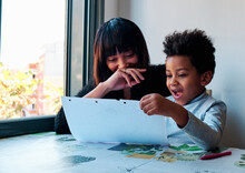 Caring Ethnic Mother Sitting With Curious Child And Drawing On Paper Together While Enjoying Weekend At Home