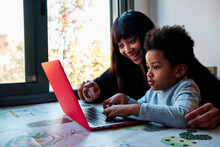 Cheerful Black Mother Sitting At Table With Curious Boy And Playing Together Interesting Video Game On Laptop At Home
