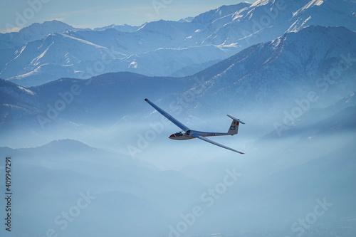 Glider in flight between snowy mountains seen from above Fototapeta