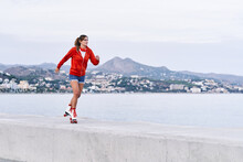 Side View Of Female In Trendy Outfit Riding Roller Skates Along Stone Promenade On Background Of Sea