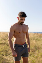 Determined Male Athlete With Strong Naked Torso Standing On Grassy Hill On Sunny Day In Summer And Looking Down