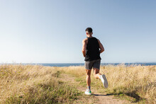 Muscular Male Jogger Running Along Path In Meadow During Training On Background Of Sea In Summer