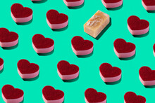 From Above Full Frame Composition Of Red Heart Shaped Soap Arranged In Order On Light Green Background With One Different
