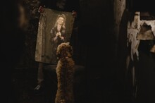Playful Dog Looking At Painted Portrait Of Happy Woman Held By Anonymous Person In Dark Room