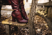 Side View Of Crop Anonymous Female In Stylish Elegant Leather Boots Standing On Old Stone Bench In Autumn Park